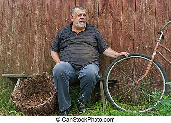 Ukrainian senior farmer sitting on a bench