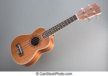 Ukulele guitar on gray background