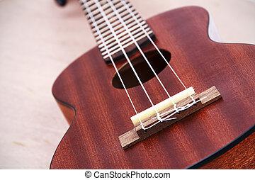 Ukulele guitar on wooden background