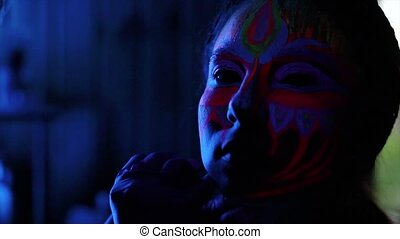 Ultraviolet black light glowing bodyart processing on young...
