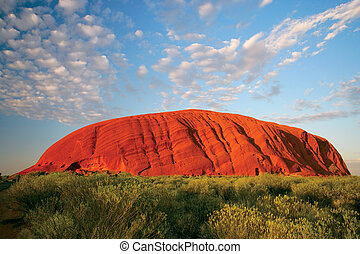 Uluru early in the morning as the sun turns it bright red.
