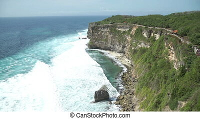 Uluwatu stone cliffs, ocean waves. Aerial top view. Bali,...