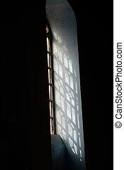 um, alto, janela arqueada, com, um, vindima, metal, grille, ligado, um, pretas, parede, córregos, de, disperso, luz solar, fluxo, através, a, janela.