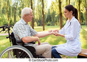 um, doutor mulher, medidas, a, pulso, de, um, idoso, paciente, ligado, um, cadeira rodas