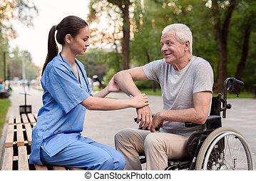 um, enfermeira, cuidadosamente, examina, a, cotovelo, de, um, idoso, paciente, ligado, um, banco, parque