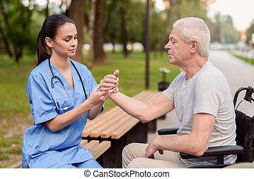 um, enfermeira, examina, a, pulso, de, um, idoso, paciente, quem, senta-se, logo, ligado, um, cadeira rodas