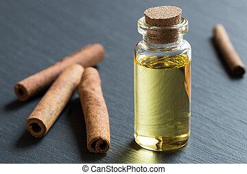 um, garrafa, de, canela, óleo essencial, com, varas canela, em, a, fundo