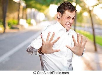 um, homem jovem, segurando, seu, mãos, em, medo