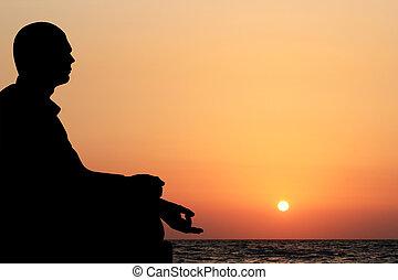 um, homem jovem, sentar posição lotus, e, meditar, ligado, um, praia, em, a, noite, com, sol, armando, em, a, experiência., a, céu, é, laranja, amarela, e, a, oceânicos, lata, também, ser, visto, em, a, meditação, fundo
