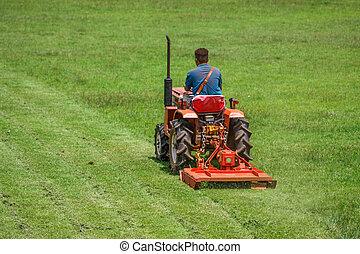 um, homem, ligado, mower, grama cortante, em, campo futebol americano
