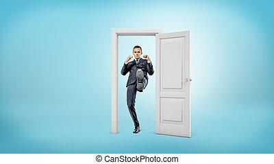 um, jovem, homem negócios, plataformas, em, um, pequeno, recorte, doorframe, e, pontapés, um, porta aberto, com, seu, foot.