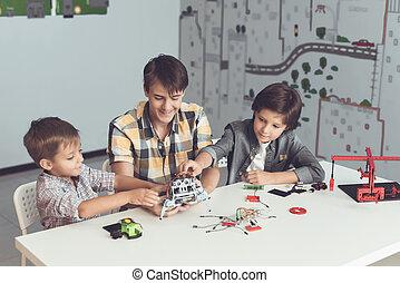 um, jovem, sujeito, mostra, dois meninos, como, montar, um, robot., eles, observar, e, ajuda, com, interesse