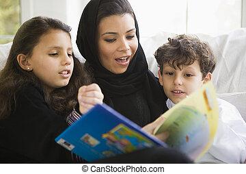 um, meio oriental, família, lendo um livro, junto