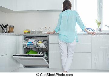 um, mulher, em, branca, calças brim, e, um, turquesa, camisa, plataformas, com, dela, costas, perto, um, abertos, dishwasher, em, um, branca, cozinha, interior, frente janela