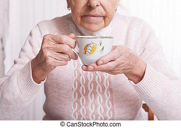 um, mulher idosa, bebidas, chá, em, home., mulher sênior, xícara segurando, de, chá, em, seu, mãos, tabela, closeup