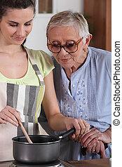 um, mulher sênior, olhar um, mulher jovem, cozinhar