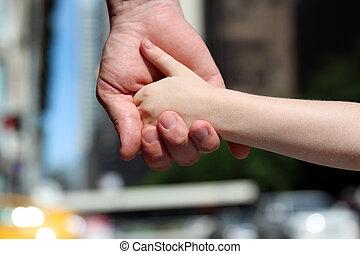 um, pai, segura, a, mão, de, um, criança pequena, ao ar livre
