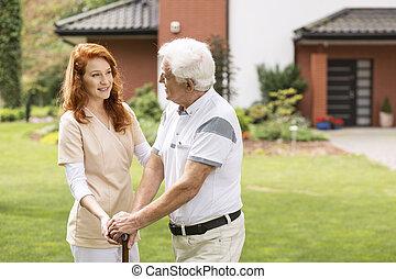 um, profissional jovem, enfermeira, em, uniforme, ajudando, um, homem idoso, com, cana, exterior, seu, home.