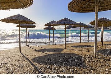 Umbreles on the sand beach with cloudy sky and sun