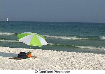 Umbrella - An unoccupied beach umbrella shades an empty mat...