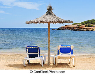 umbrella and sunloungers in Ibiza, Spain