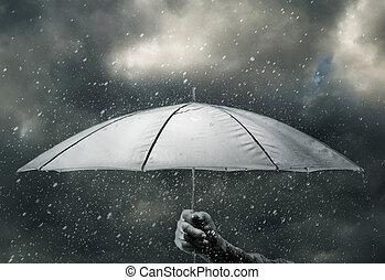 Umbrella in hand under raindrops of thunderstorm
