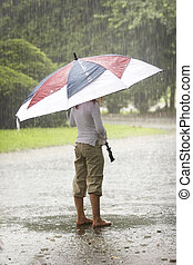 Umbrella in the rain - A young bare foot person standing and...