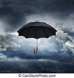 Umbrella - Old black umbrella against rainy sky.