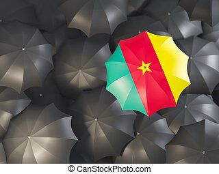 Umbrella with flag of cameroon on top of black umbrellas. 3D illustration