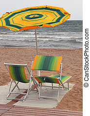 umbrellas and sunbeds on the beach during a windy day