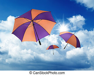 Umbrella's falling from a blue sky with white Cumulus Clouds