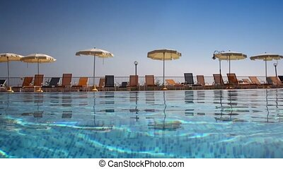 Umbrellas near pool, camera is on wavy water surface, after...