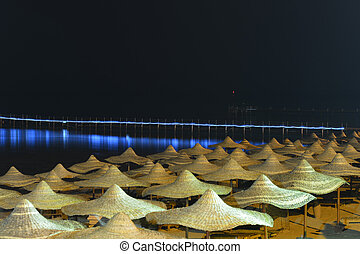 Umbrellas on beach at night