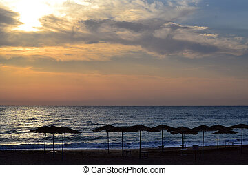 Umbrellas on the beach at sunrise