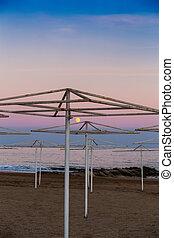 Umbrellas on the beach at sunset.