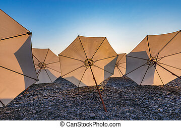 Umbrellas on the stone beach at sunset time.