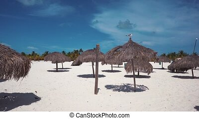 Umbrellas on the white sandy beach of Cayo Largo, Cuba. Azure water and white sand.