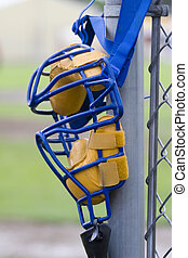 Umpire's mask hanging on backstop post, waiting for game to start.