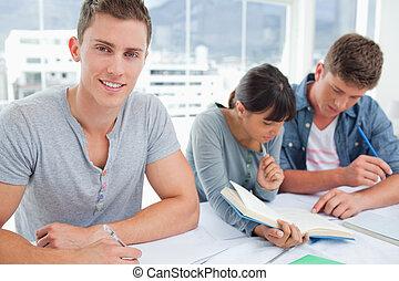 un, estudiante masculino, investigar la cámara, y, sonrisa, como, el, otro, estudiantes, sentarse, y, mirar, su, libros