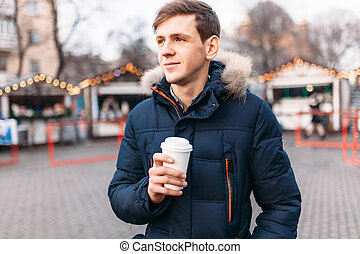 un, guapo, hombre, en, un, chaqueta, tenencia, un, taza de plástico, café de bebida, o, té, es, frío, exterior