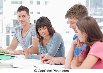un, hombre sonriente, miradas, en, el, cámara, como, el suyo, otro, amigos, sentarse, y, estudio, y, escribir