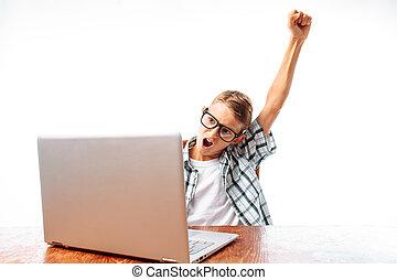 un, joven, el sentarse en una tabla, con, un, computador portatil, feliz, victoria, levantar, el suyo, entregue arriba, sentado, en, el, estudio, en, un, fondo blanco, en, el, estudio