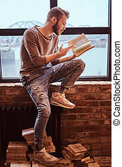 un, joven, guapo, estudiante, con, elegante, barba, y, pelo, leer un libro, mientras, sentado, en, un, alféizar