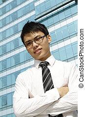 un, joven, negocio asiático, ejecutivo, posición, delante de, un, edificio de oficinas