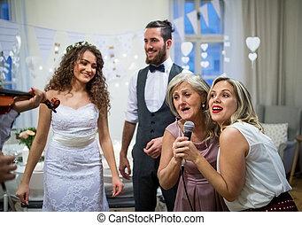 un, joven, novia y novio, con, otro, huéspedes, bailando, y, canto, en, un, boda, recepción.