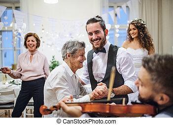 un, joven, novio, bailando, con, abuela, en, un, boda, recepción.