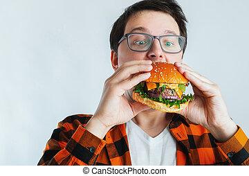 un, joven, tipo, con, anteojos, tenencia, un, fresco, burger., un, muy, hambriento, estudiante, come, rápido, comida., caliente, provechoso, comida., el, concepto, de, glotonería, y, malsano, diet., con, espacio de copia, para, texto