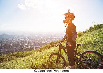 un, joven, tipo, posición, en, su, bicicleta montaña, encima de, un, montaña, cuándo, debajo, el, montañas, nubes bajas