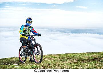 un, joven, tipo, se sienta, en, un, bicicleta montaña, encima de, un, montaña, cuándo, debajo, el, montañas, nubes bajas