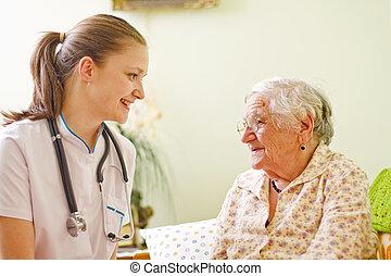un, médico joven, /, enfermera, visitar, un, anciano, mujer enferma, alternar, -, hablar, -, con, ella.